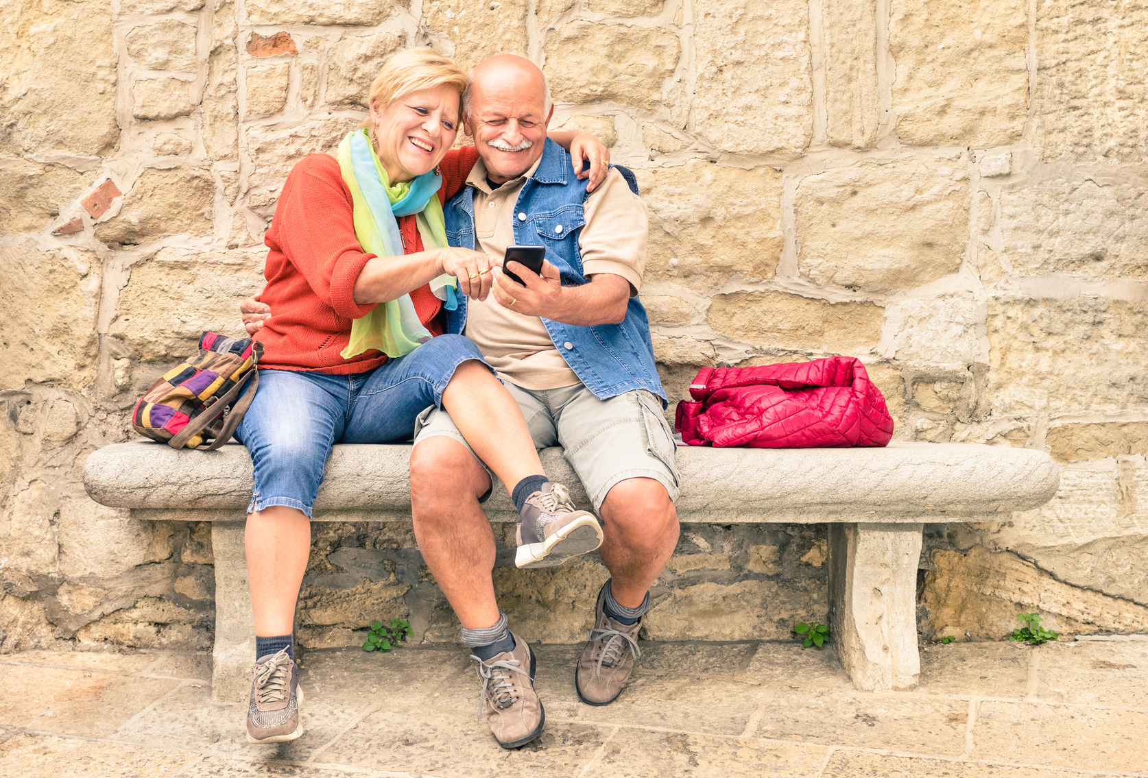 Happy senior couple having fun together with mobile smart phone - Active elderly concept with retired people